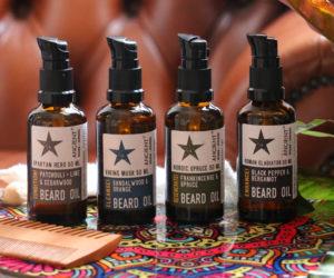 Sortiment von Bartölen - 50ml Flaschen mit Bartkamm auf buntem Hocker und Sessel