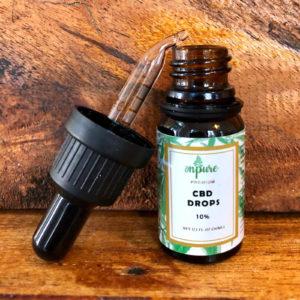 CBD Drops 10% von onpure - 10ml Flache mit Pipette auf Holz Hintergrund